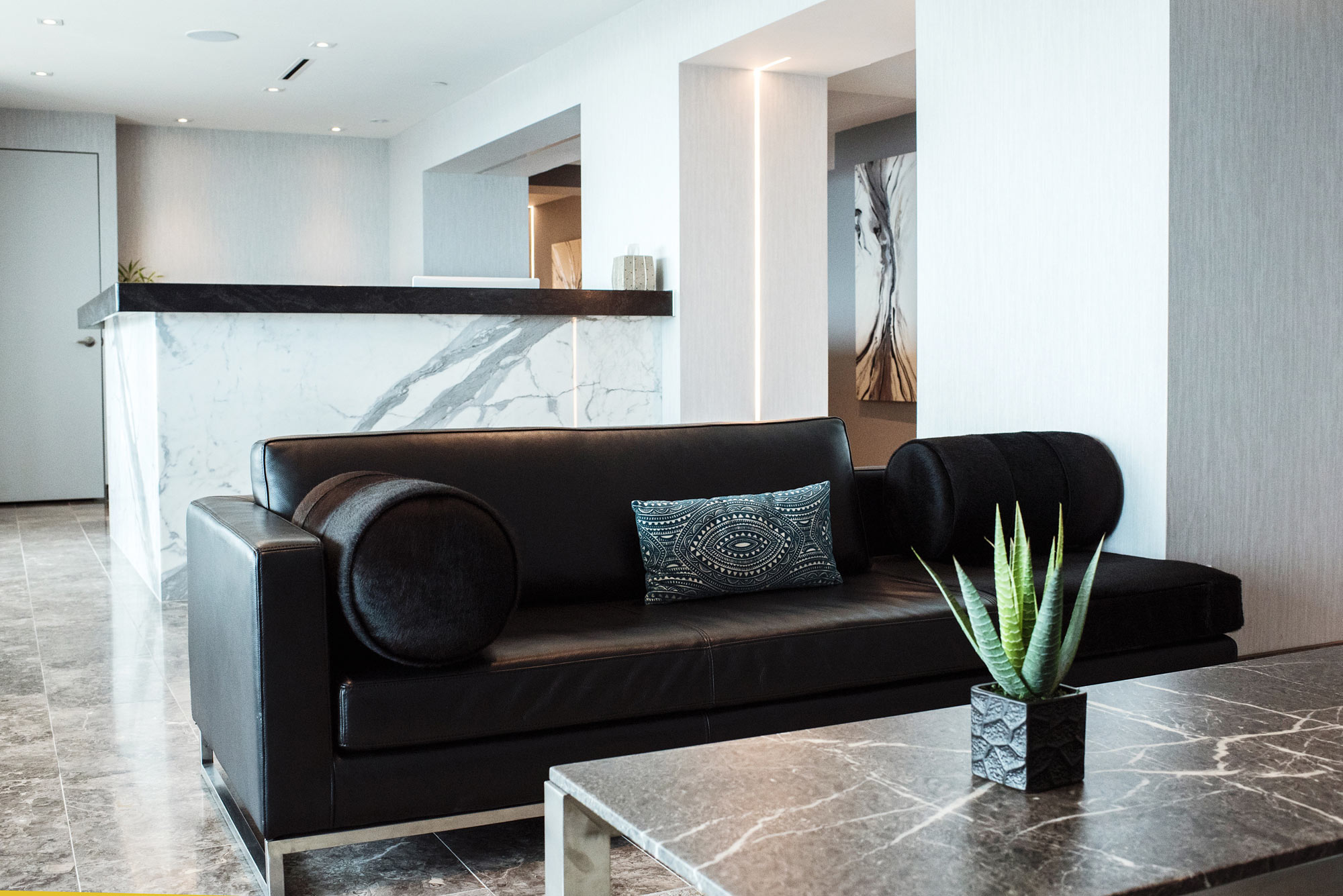 Modern office space building lobby with black couch and marble front desk