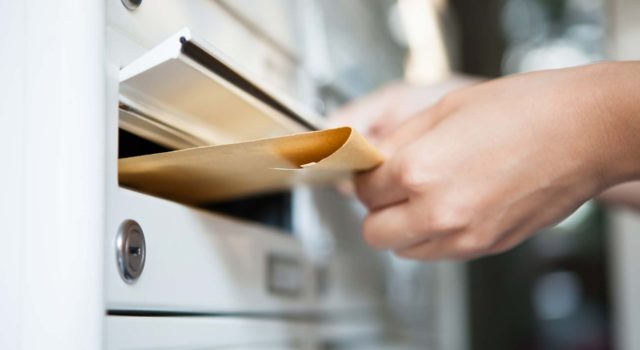 a hand putting an envelope into a mail slot